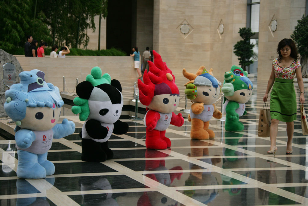 Small cherubit Olympic mascots with a woman walking by