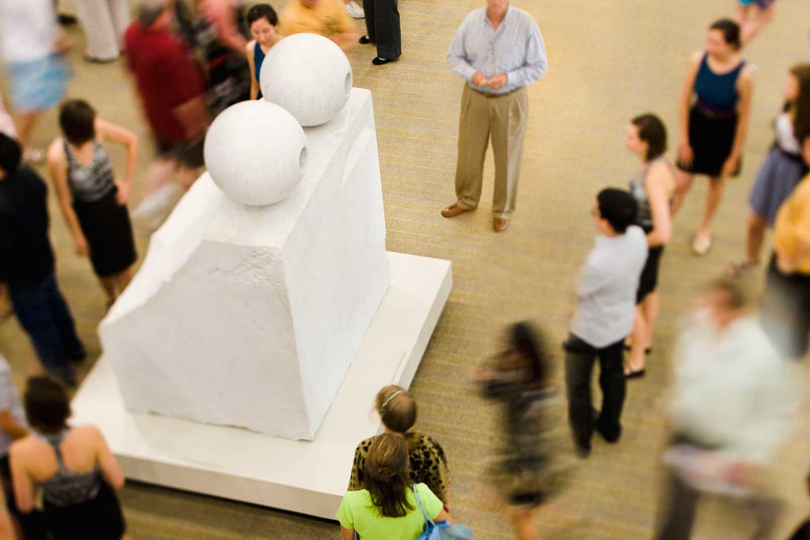 A large white marble sculpture in a room surrounded by people.