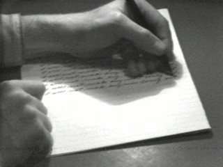 A person writing on a piece of paper.