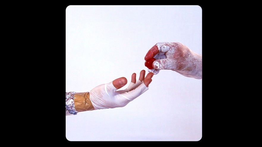 A hand with fingerless gloves reaching out to a hand with dried paint on it