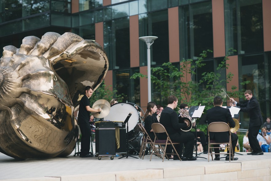 Musicians playing in front of bronze sculpture of shell