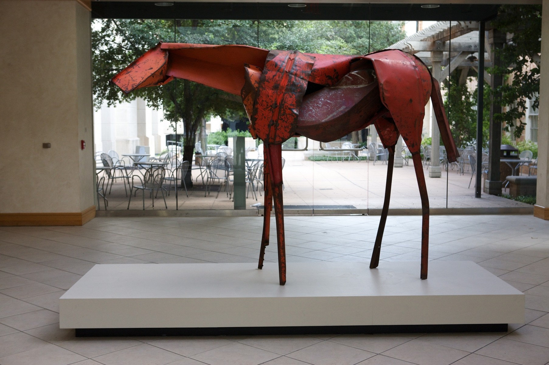 A red horse sculpture in front of a large window