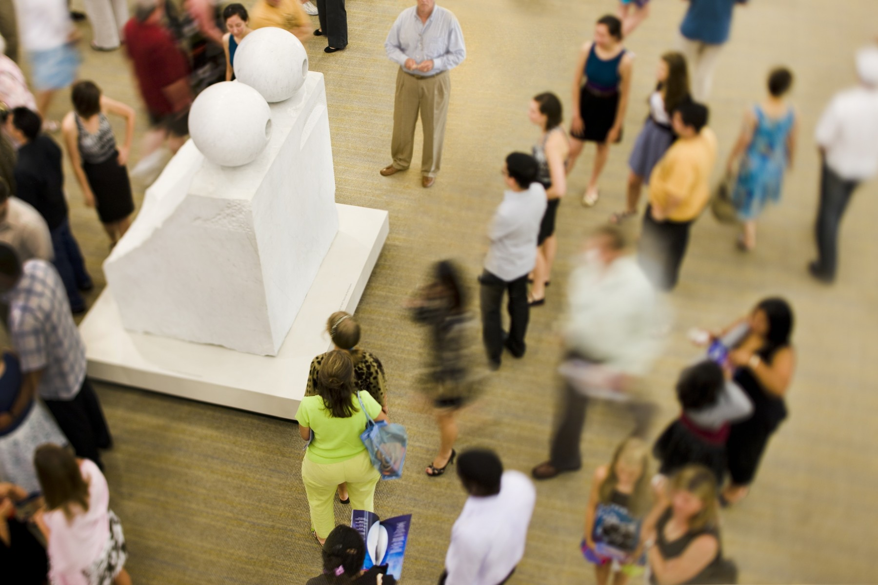 A crowd of people around a large rectangular marble sculpture with spheres on top