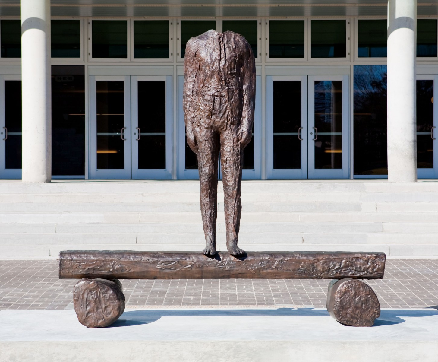 Headless statue in front of a large building