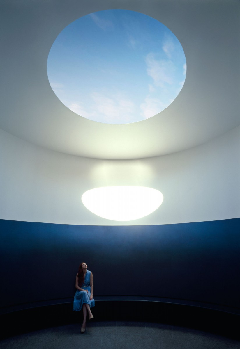 The sun shining through an oculus near a seated woman