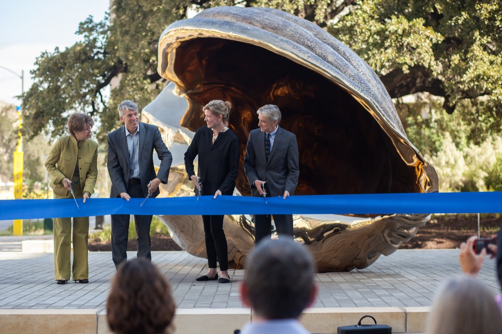 Four people about to cut a large ribbon in front of a bronze shell