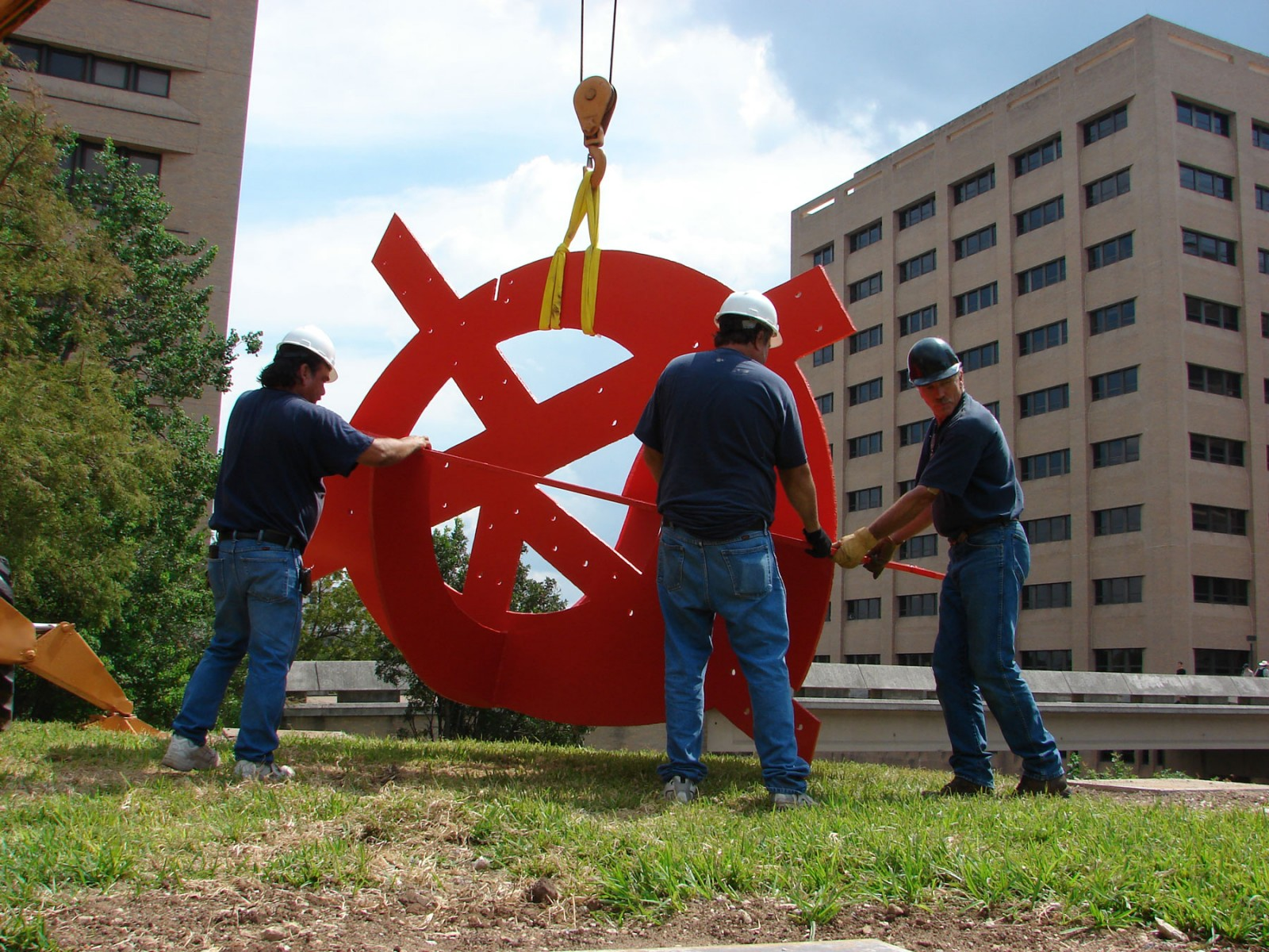 Men working on a large red metal sculpture