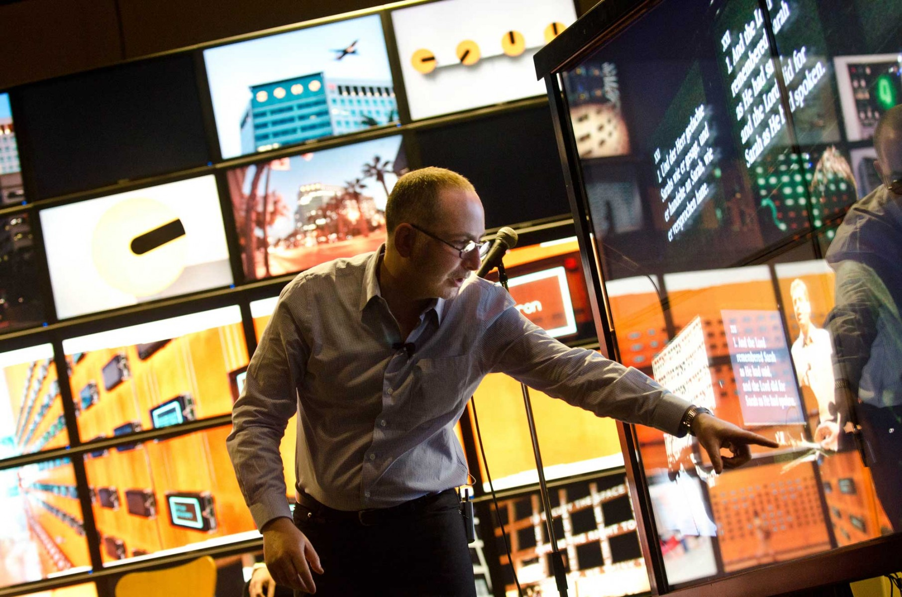 A man pointing in front of digital screens