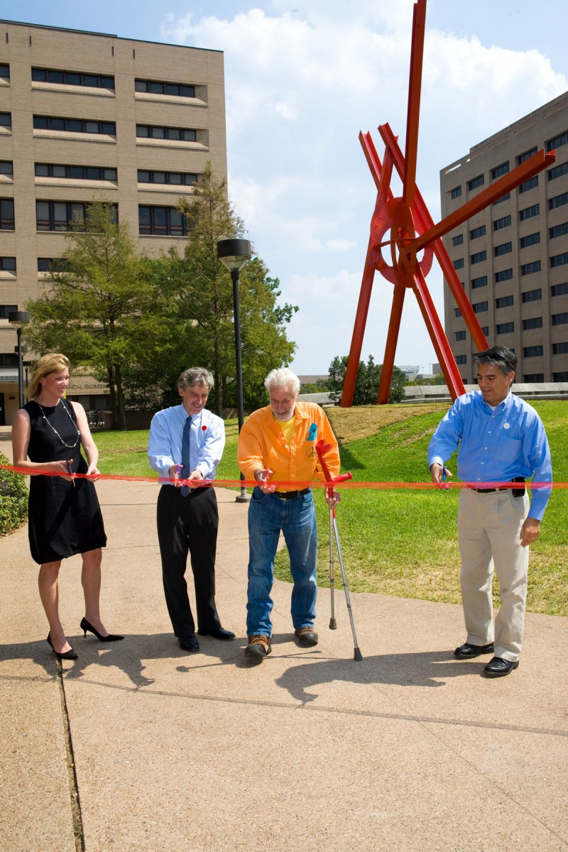 Four people cutting a ribbon in front of a large metal sculpture