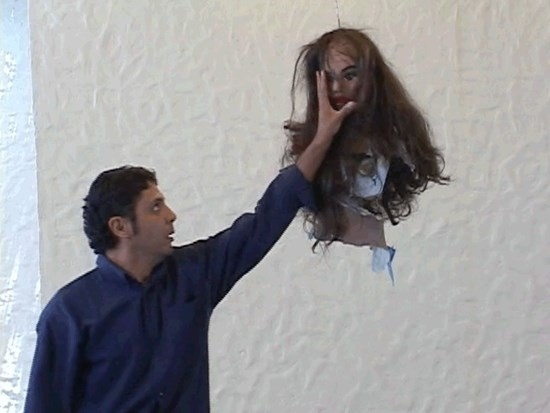 A man grabbing the face of a piñata resembling the top half of a woman
