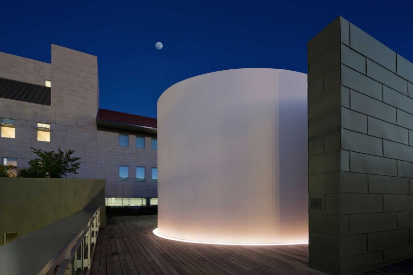 A giant cylinder on a deck in front of the night sky.