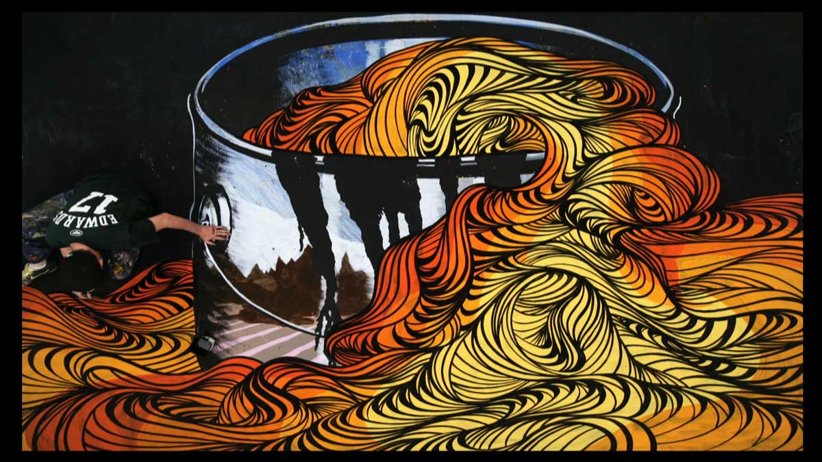 A man painting a large shiny bucket with long colorful pasta flowing out