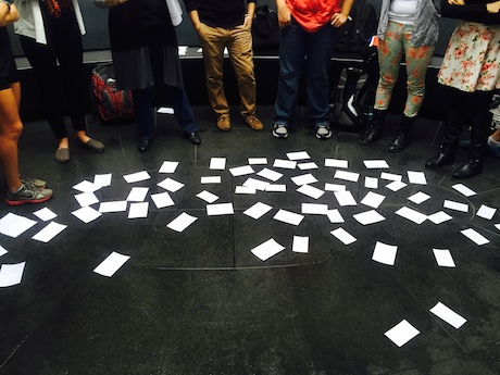 Papers scattered on the floor with students standing around them