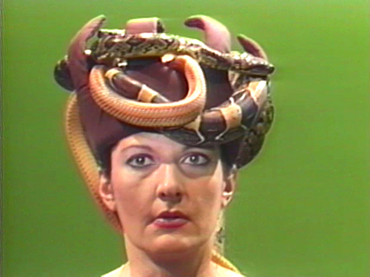 A woman with a hat covered in snakes.