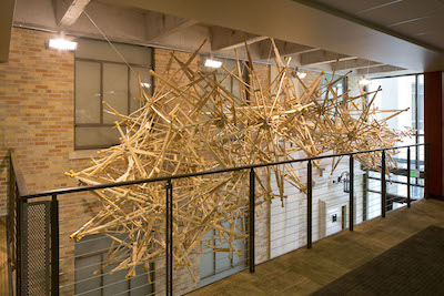 Wooden crutches combined into a spoke pattern hanging from the ceiling of an atrium
