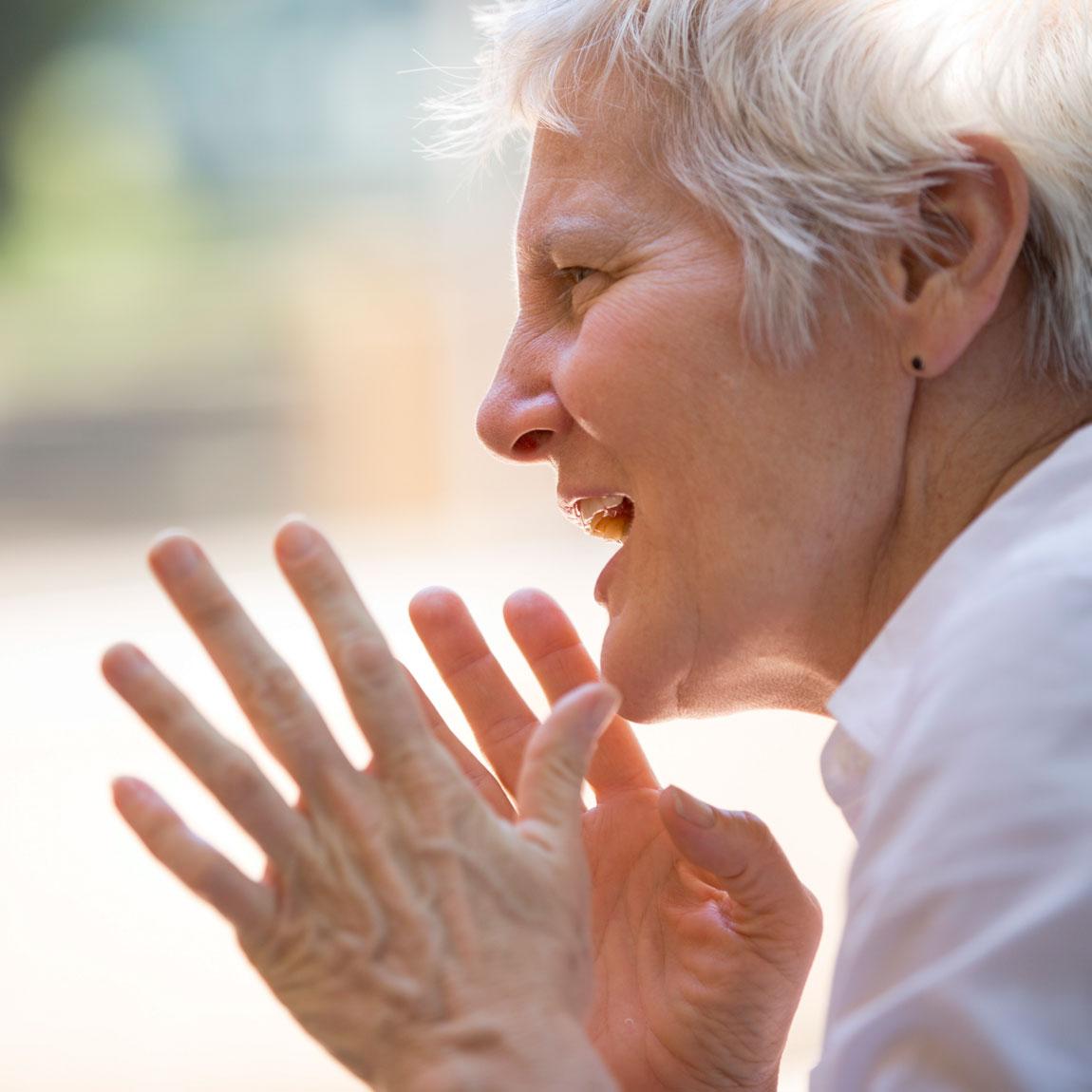 A woman in a linen shirt gesticulating