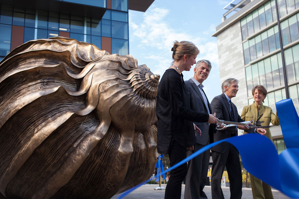 Four people cutting a ribbon in front of large bronze shell sculpture