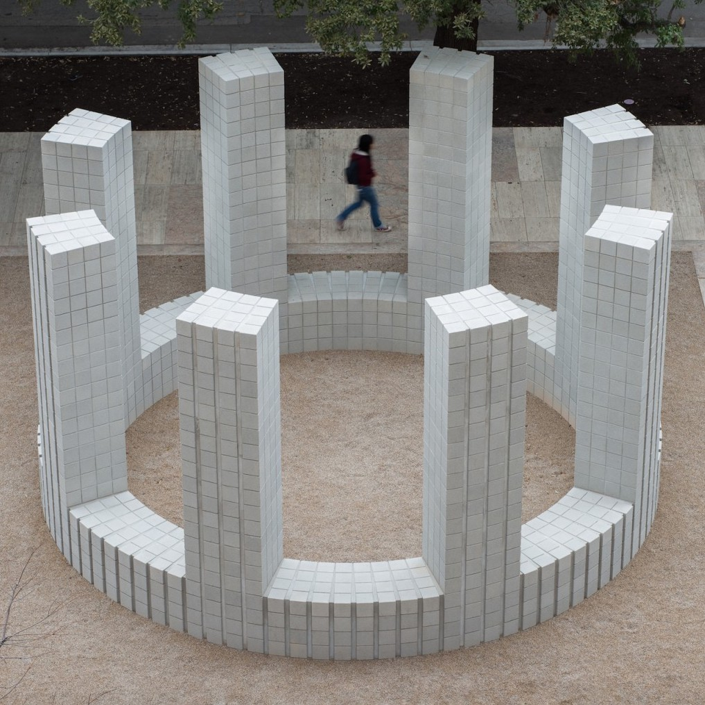 A circular structure of white concrete brick with 8 pillars seen from above