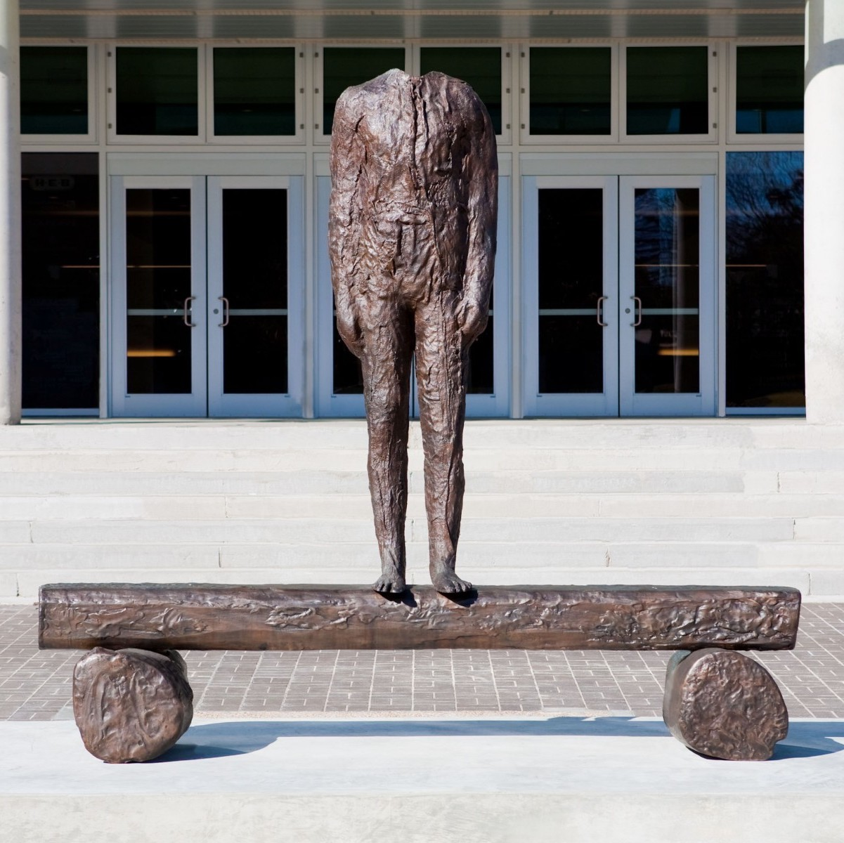 A headless figure stands on a flat surface supported by two wheels which look like tree trunks. The work is cast bronze and hollow when viewed from the other side