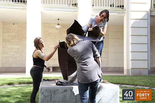 Three women stand around a sculpture cleaning and conserving it, with UT's 40 for 40 logo in the bottom right corner