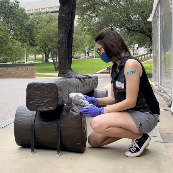Ali Wysopal wearing a mask kneels down and rubs a bronze sculpture with a cloth.