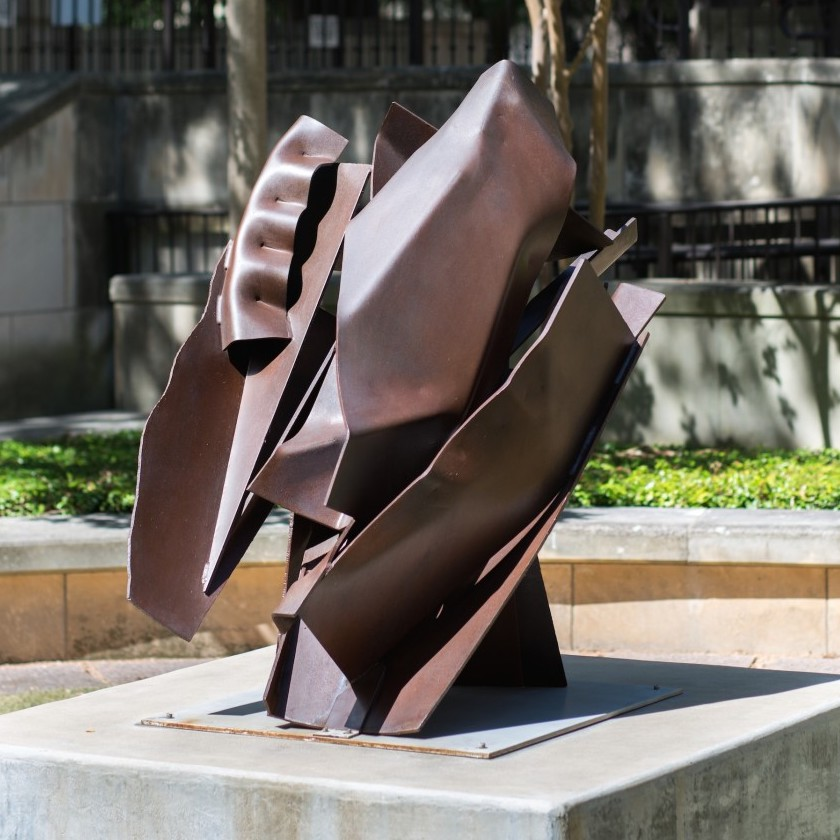 A steel sculpture that is composed of many welded together parts, the work is a dark brown.