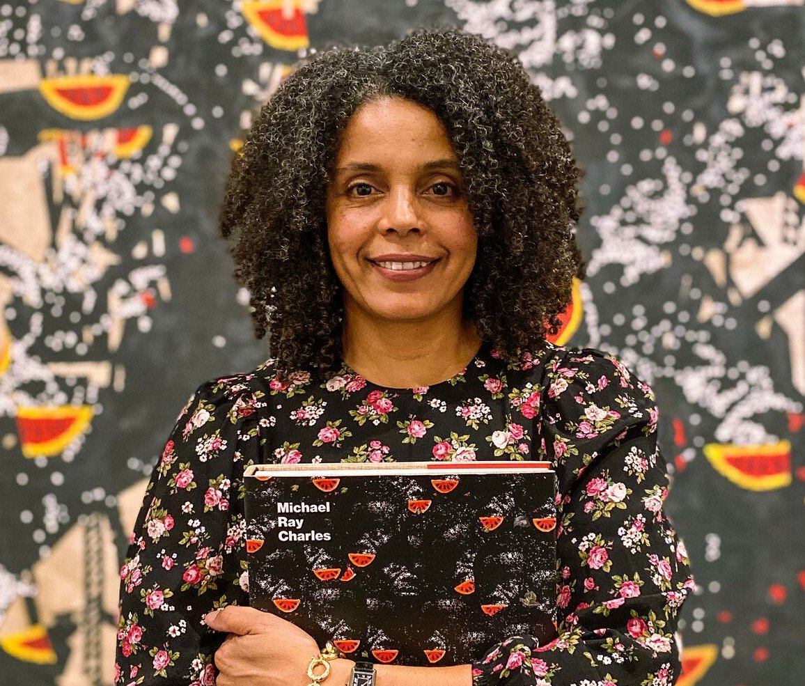 An image of Dr. Cherise Smith holding a copy of her book