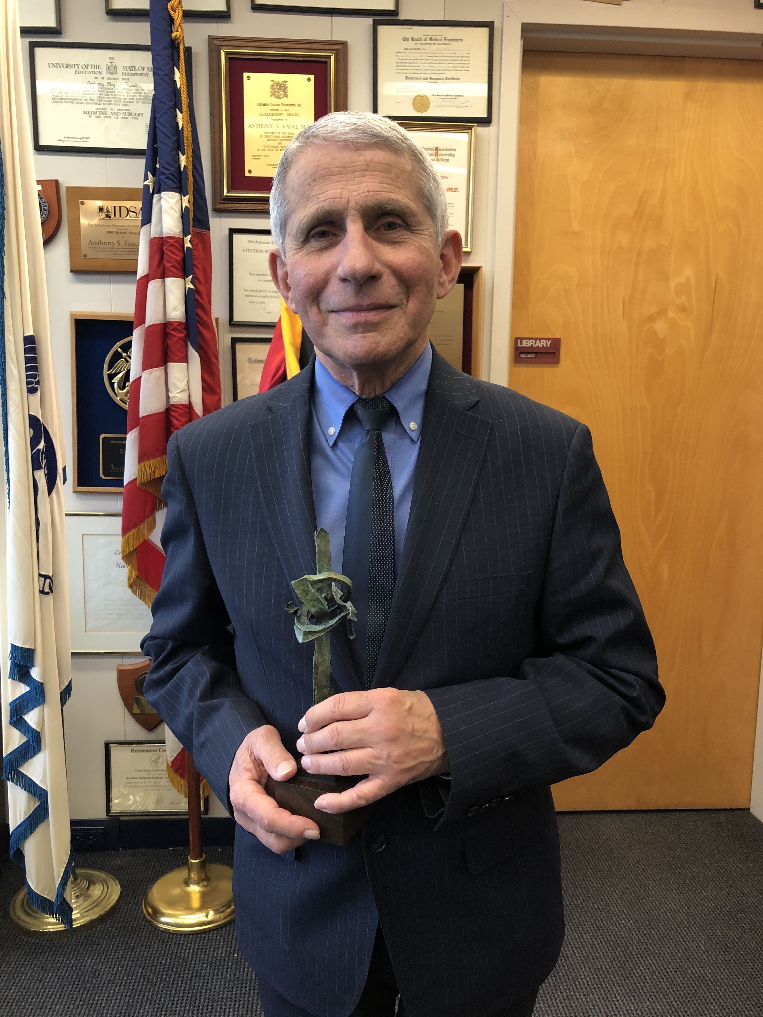 "Photo shows older gentleman (Dr. Fauci) holding a small replica of Seymour Lipton's ""Pioneer"" in his hands. He stands in an office with an American flag in the background"
