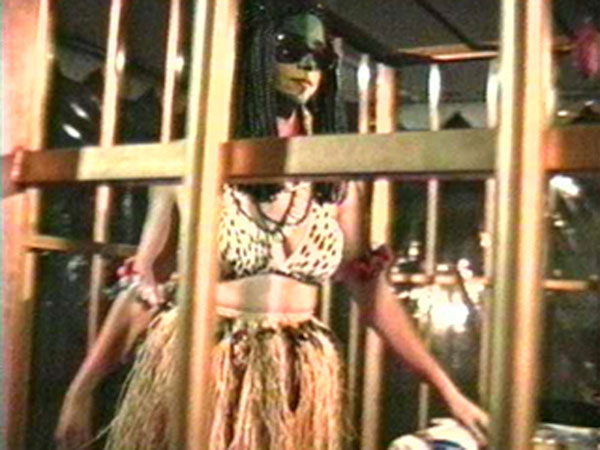 A woman wearing sunglasses and a grass skirt inside of a cage.