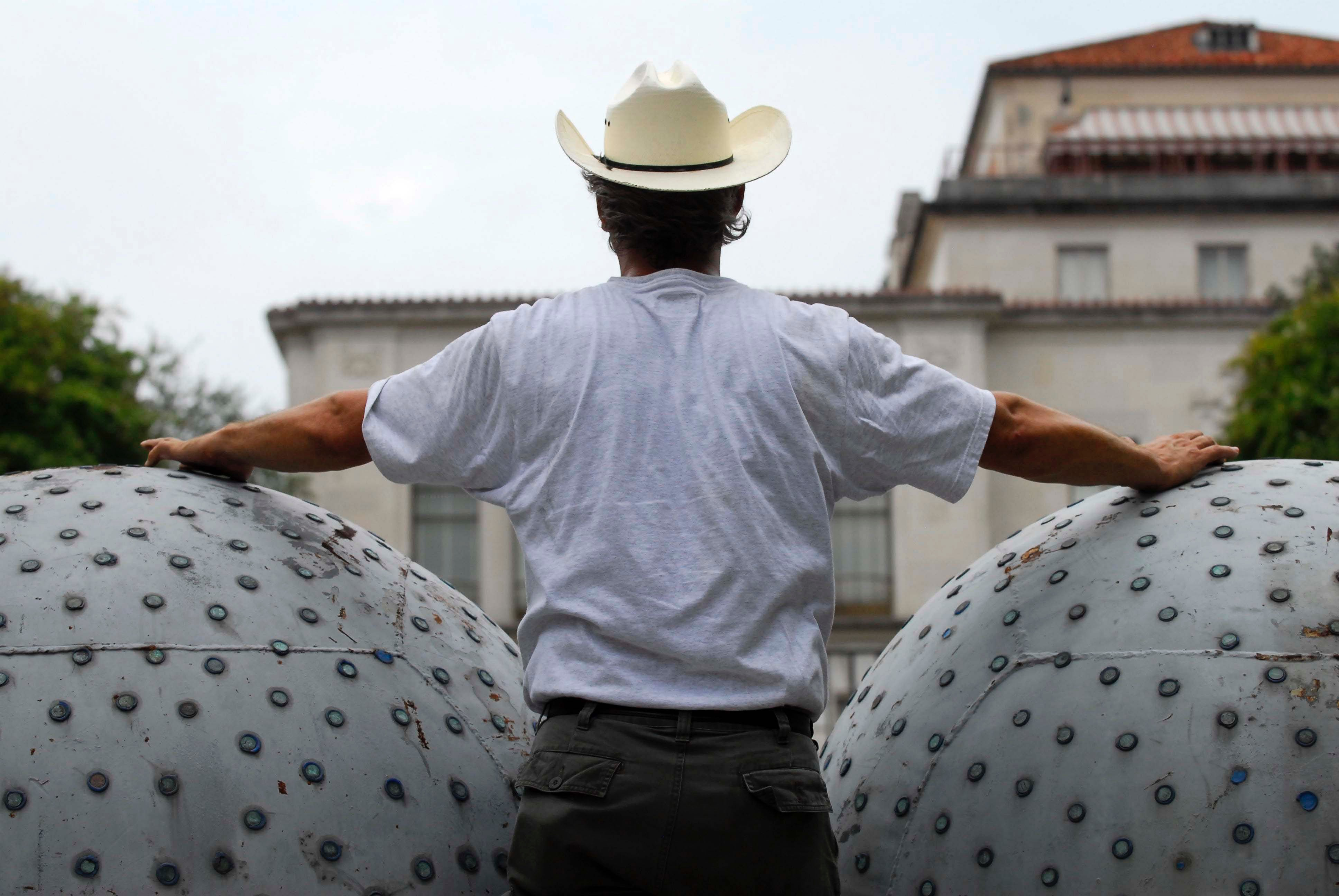 A man wearing a cowboy hat stands between the two large buoys that make up Donald Lipski's The West