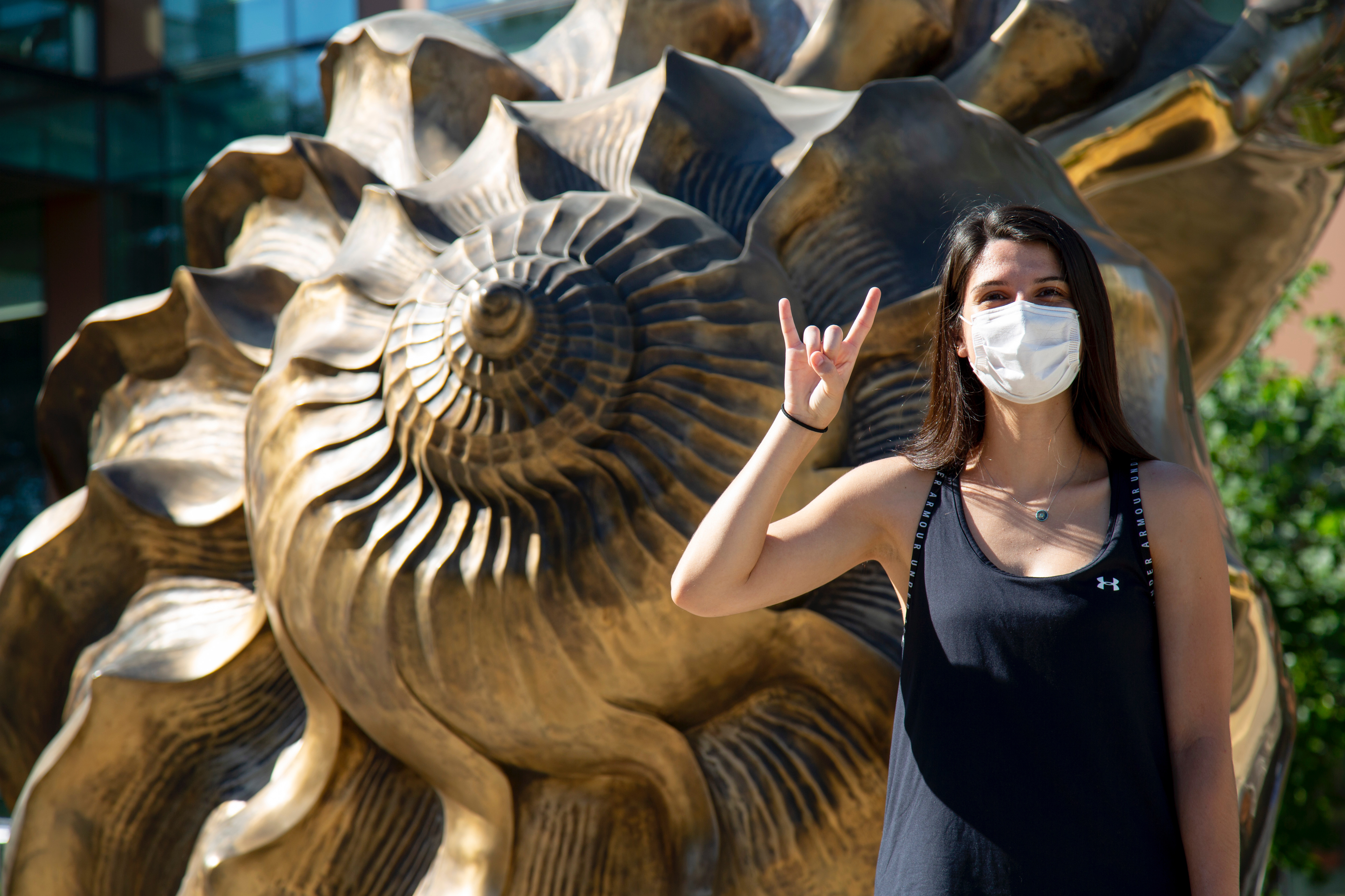 """A woman in a mask makes a """"hook em"""" gesture and looks at the camera in front of Marc Quinn's sculpture """"Spiral of the Galaxy"""" which is an enlarged bronze seashell"""