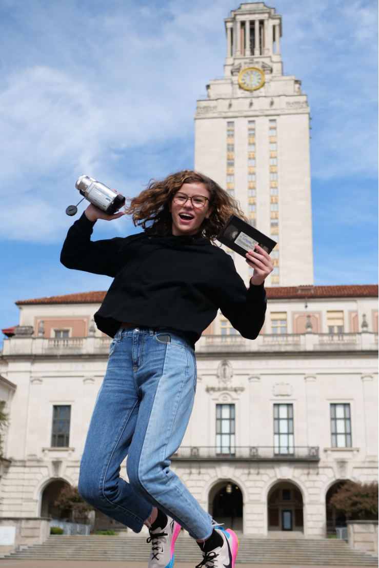 Photo is of a young girl jumping up in the air while holding a video camera in her right hand and a tape in her left hand. In the background shows the UT Austin Tower behind her.