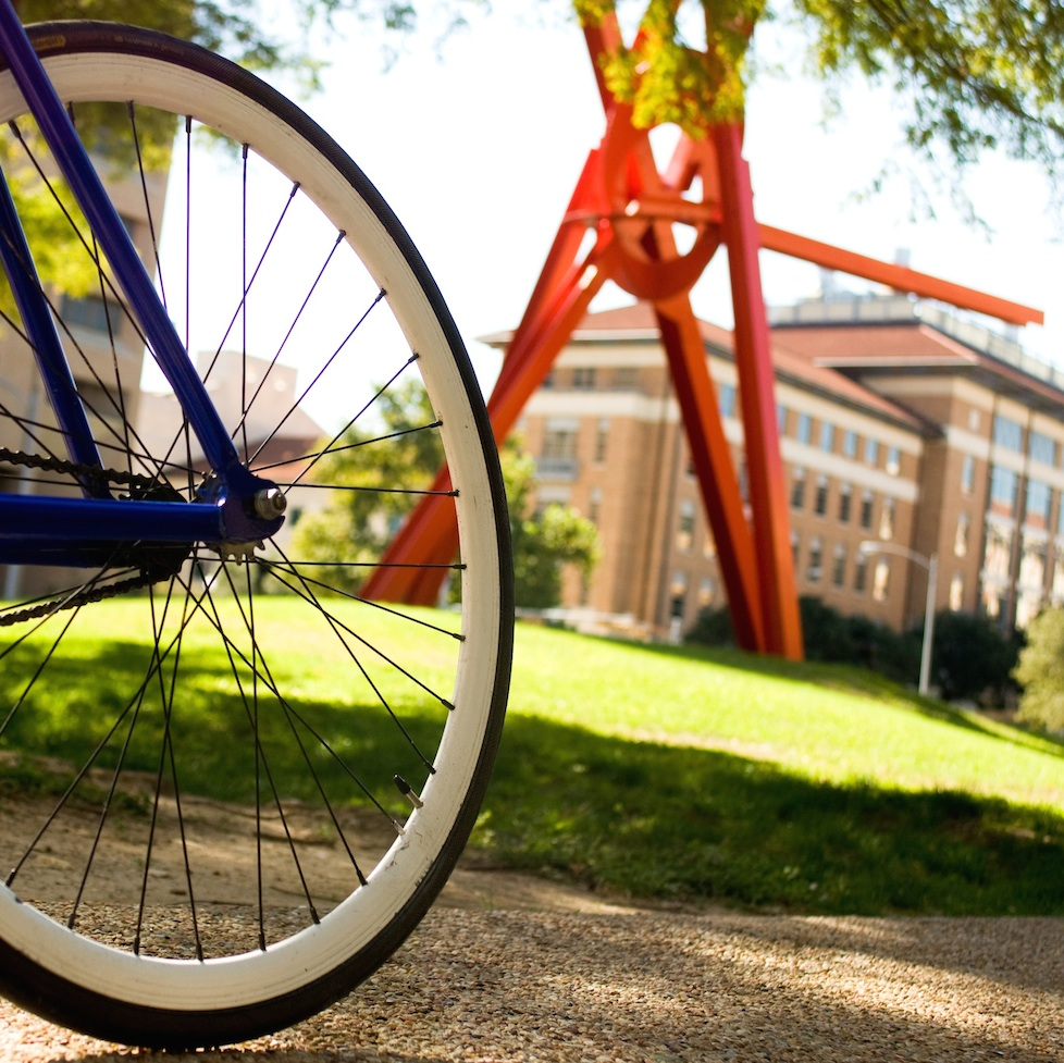 The wheel of a bicycle in front of a metal sculpture