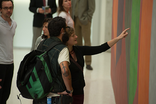 Two people pointing at Lewitt Wall Drawing