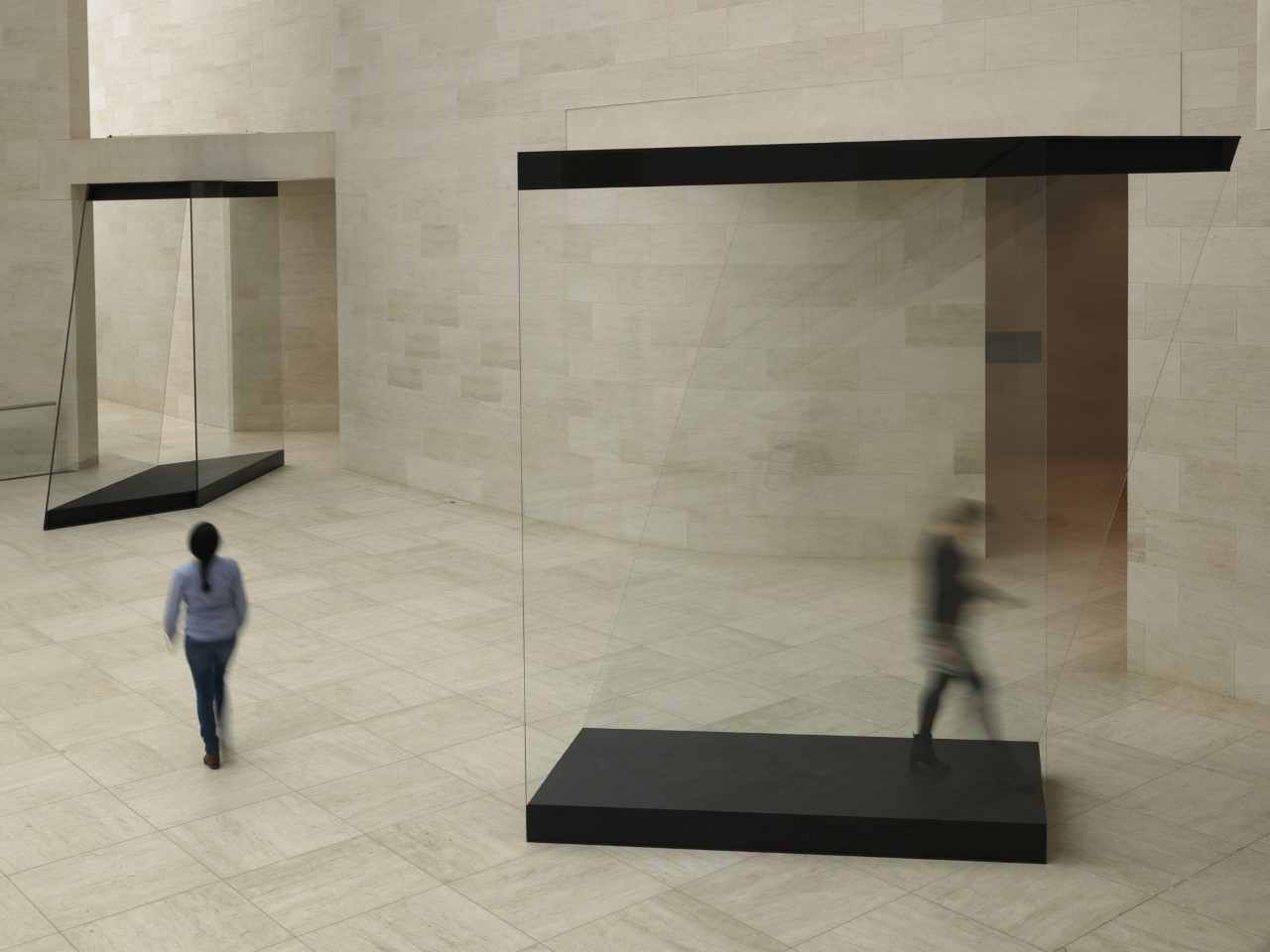 Two glass and wood structures in the atrium of a museum. A person can be seen walking through one and another person is walking towards another. Both figures are slightly blurred showing movement.