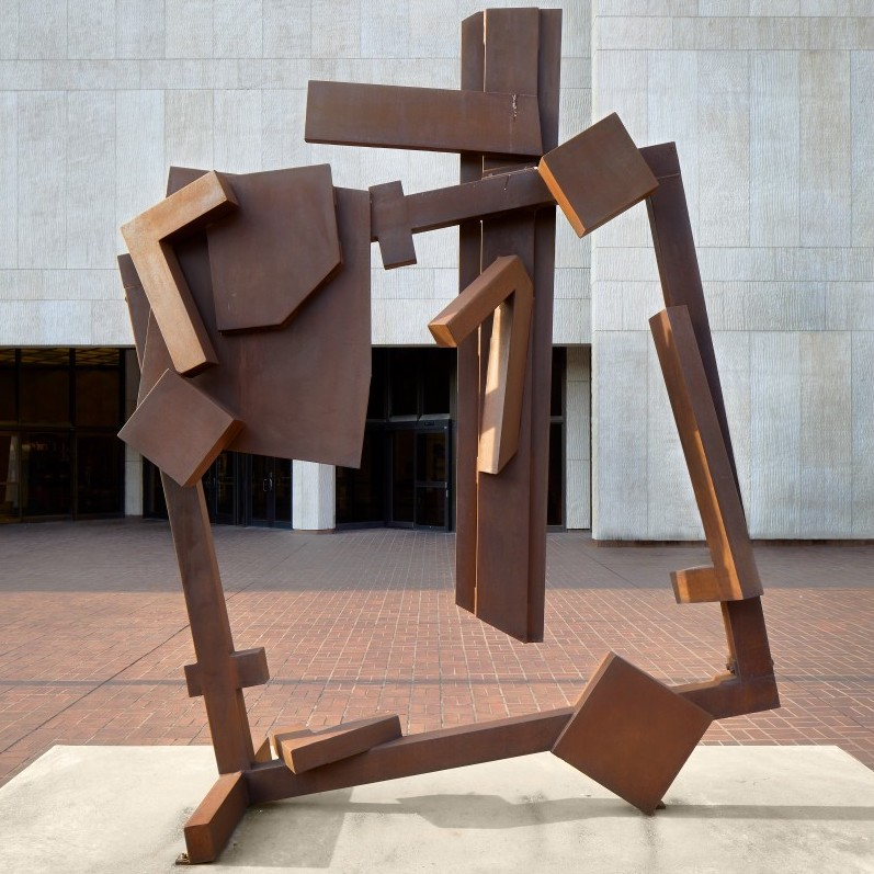 A steel sculpture that has elements welded to a main square frame which has been slightly tilted