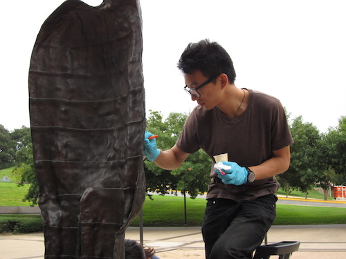 student waxing bronze sculpture