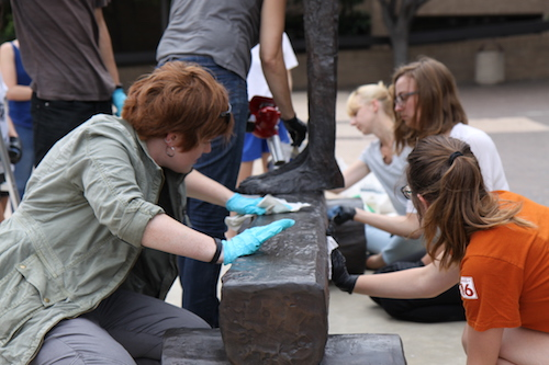 students waxing a bronze sculpture