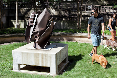 people walking dogs in front of sculpture
