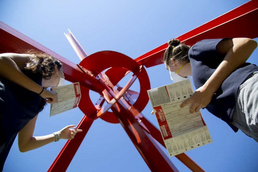 """Two women in masks holding Landmarks maps look up at Mark Di Suvero's sculpture """"Clock Knot"""""""