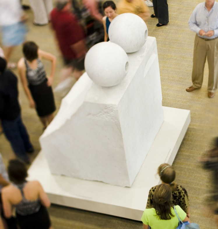 """An image of Louise Bourgeois' sculpture """"Eyes"""" a block of white marble with two circular carved eyes perched on top. The work is seen from above and is surrounded by a crowd of people who look and move around it"""