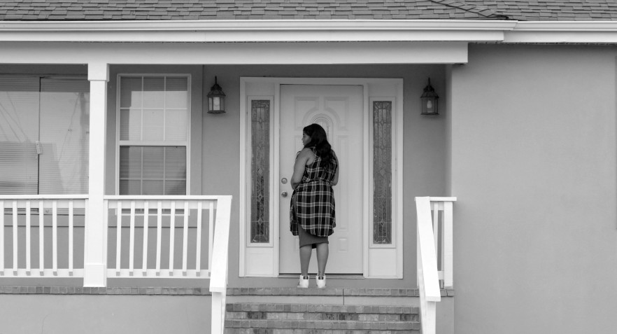 """A still from Garrett Bradley's video """"Alone"""" which shows a front porch with a female figure standing at a front door. The entire scene is in grey-scale."""