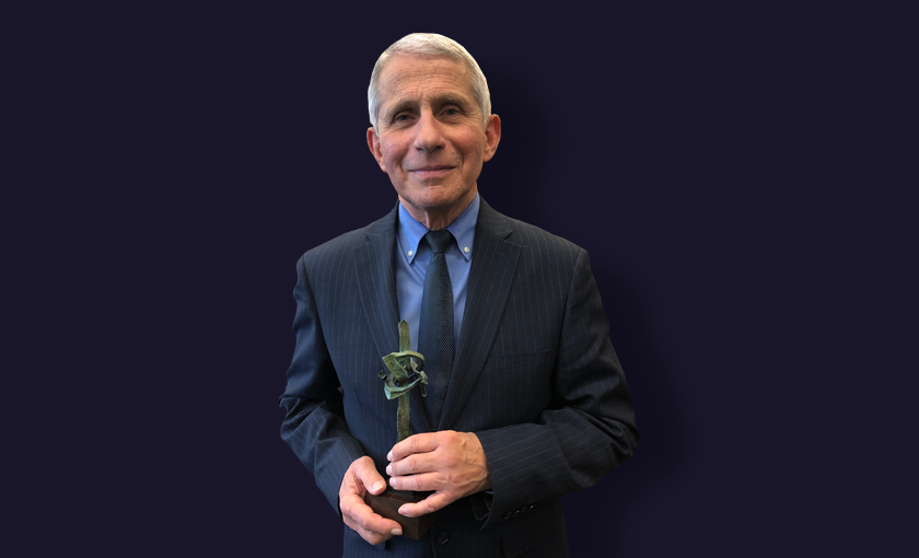 """Image is of Dr. Anthony Fauci holding a miniature replica of Landmarks collection artist, Seymour Lipton's """"Pioneer."""" Dr. Fauci stands in front of a plain navy background"""