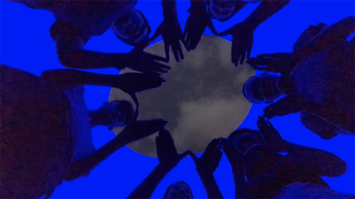 singing group putting hands together in blue tinted room