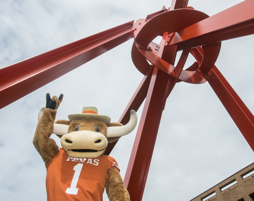 """""""Hook Em"""" UT's Longhorn Mascot, holds up a """"hook em"""" gesture in front of Mark di Suvero's """"Clock Knot"""" a large red metal sculpture that seems to meet in a mass in the upper right corner of the image"""