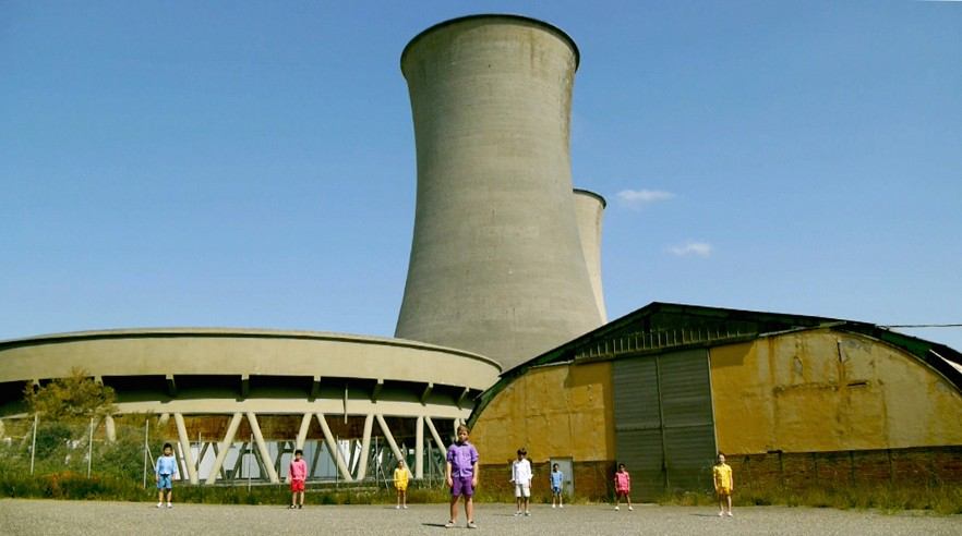 children standing in front of nuclear power plant