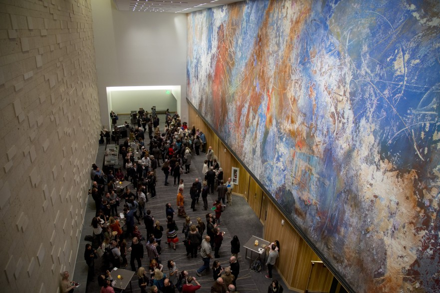 people standing under monumental mural