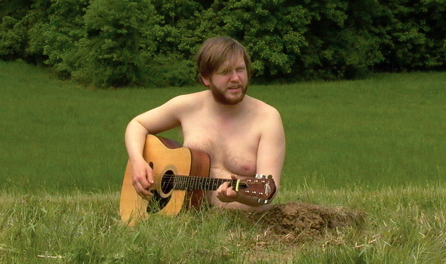 man playing guitar in field