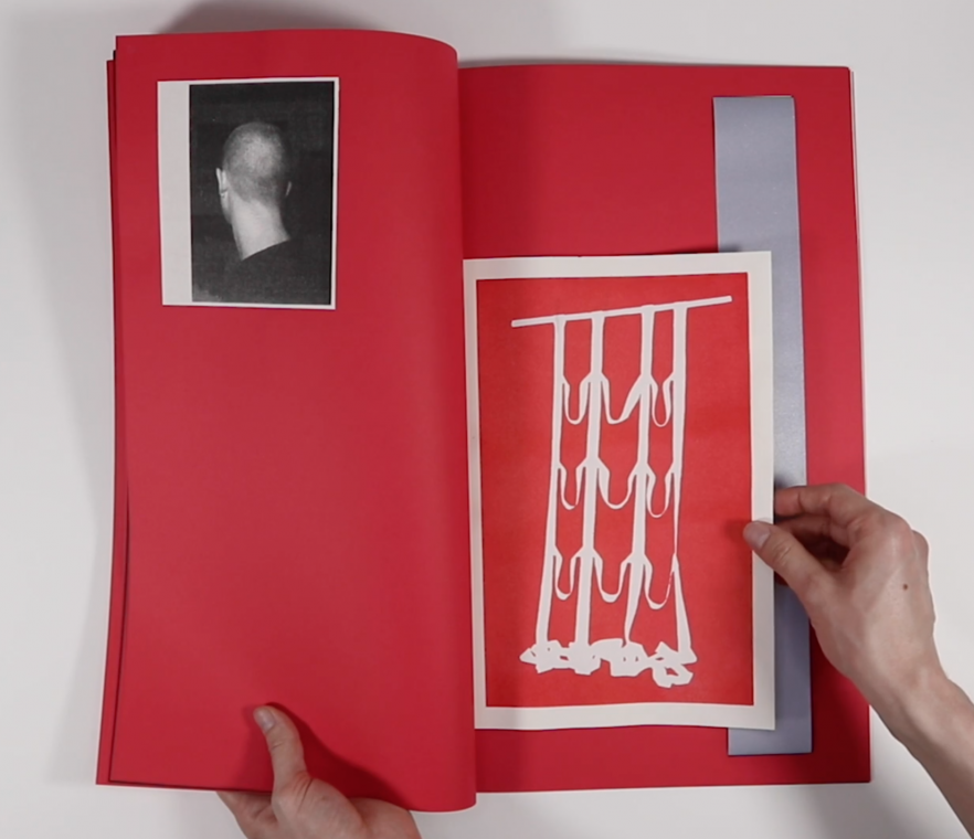 An open book which is predominantly red. On the left page there is a black and white print of the back of a head and on the right the are a red print depicting a broken grid and a strip of fabric.