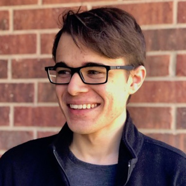 A photo of Thomas Rodriguez; He is smiling and has brown hair and black glasses on and is wearing a navy blue jacket
